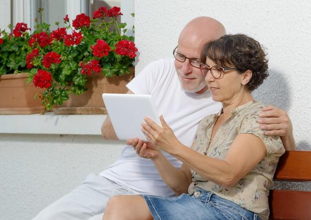 Couple de personnes âgées avec une tablette, en plein air