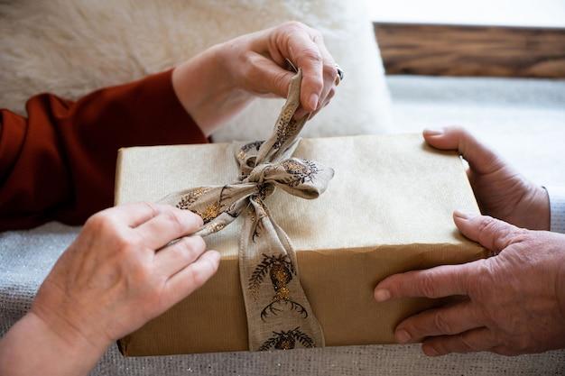 Couple de personnes âgées tenant une boîte de mains cadeau de noël