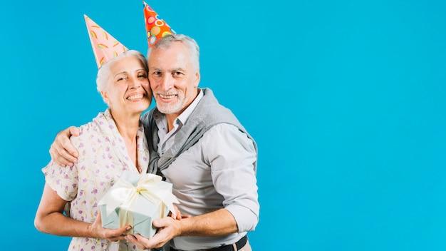 Couple de personnes âgées tenant un cadeau d'anniversaire sur fond bleu