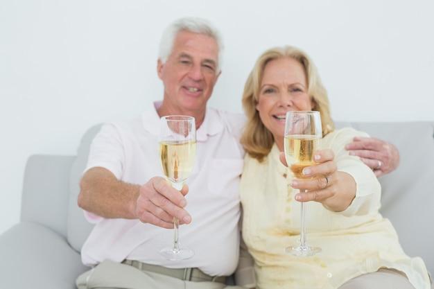 Couple de personnes âgées tenant des flûtes à champagne à la maison