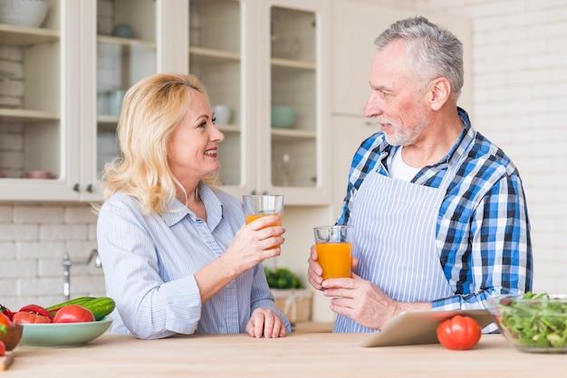 Couple de personnes âgées tenant un verre de jus se regardant dans la cuisine
