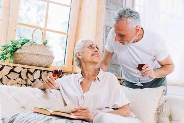 Couple de personnes âgées tenant des verres à vin dans la main, se regardant