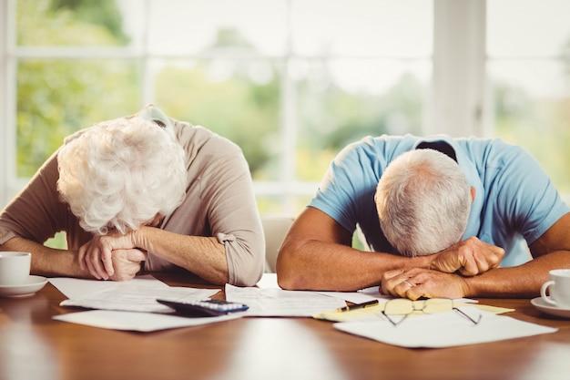 Couple de personnes âgées avec des têtes sur les bras sur une tablette tout en comptant les factures à la maison