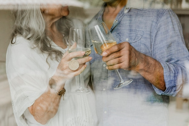 Couple de personnes âgées tinter leur verre de vin blanc