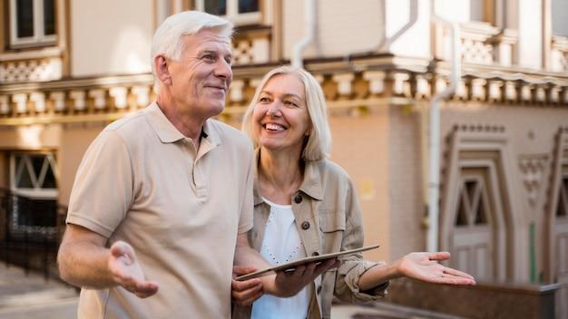Couple de personnes âgées en train de se perdre en ville et holding tablet