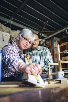 Couple de personnes âgées travaillant dans un atelier de menuiserie. mise au point sélective sur la femme en arrière-plan