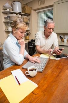 Couple de personnes âgées travaillant sur leurs factures