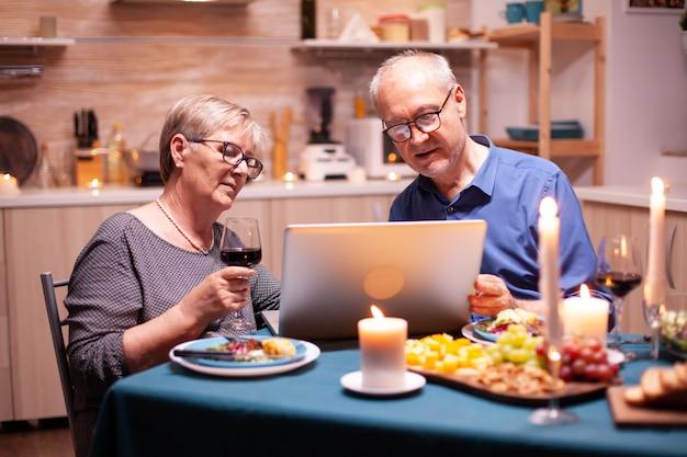 Couple de personnes âgées utilisant un ordinateur portable dans la cuisine célébrant la relation. les personnes âgées assises à la table parcourant, recherchant, utilisant un ordinateur portable, la technologie, internet, célébrant leur anniversaire dans le di