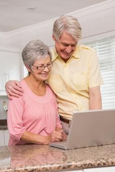 Couple de personnes âgées utilisant l'ordinateur portable ensemble
