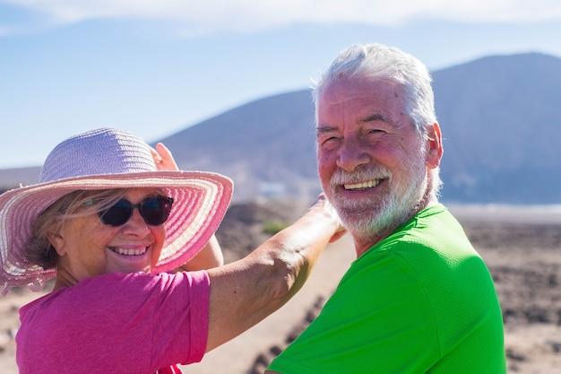 Couple de personnes âgées en vacances ensemble s'amusant - deux personnes mûres regardant la caméra en souriant et en riant - femme indiquant quelque chose avec son bras