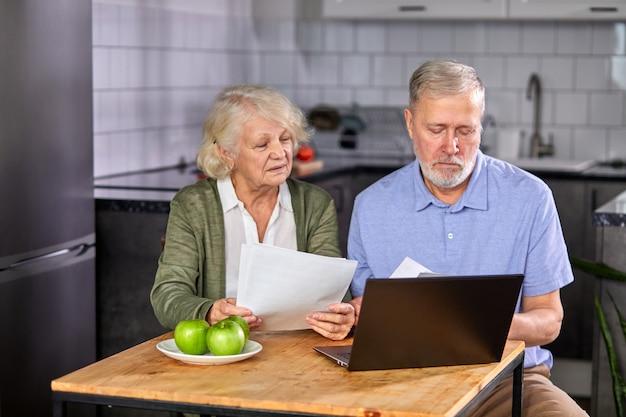 Couple de personnes âgées vérifiant les finances à la maison à l'aide d'un ordinateur portable, discutant ensemble du budget de planification, utilisant les services bancaires en ligne et la calculatrice, tenant des documents dans la cuisine