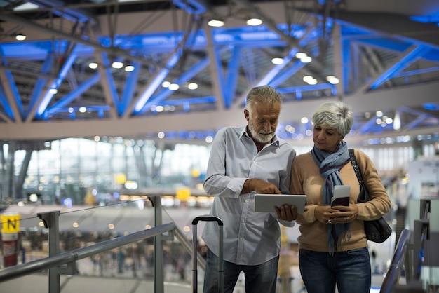 Couple de personnes âgées voyageant à l'aéroport