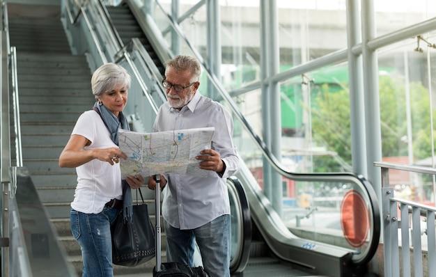 Couple de personnes âgées voyageant dans la ville