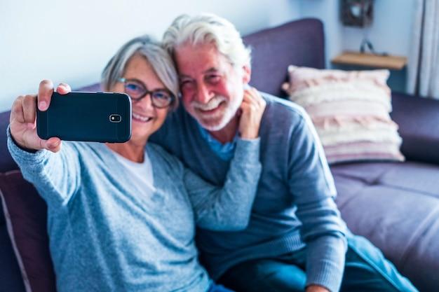 Couple de personnes mûres s'amusant à la maison assis sur le canapé prenant un selfie ensemble souriant et regardant le téléphone - deux retraités profitant de la technologie à l'intérieur