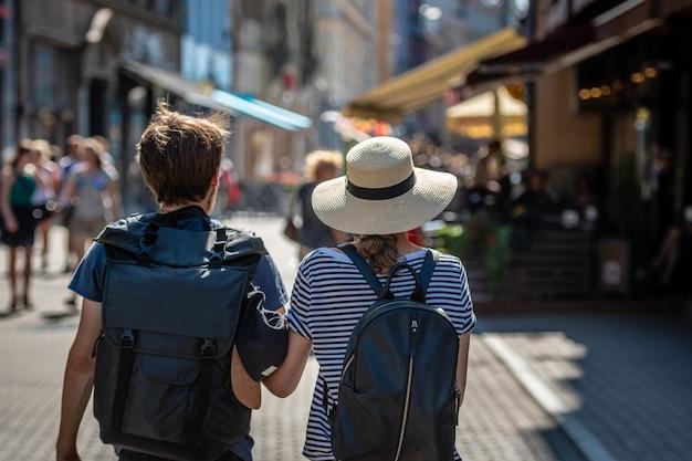 Un couple de personnes avec des sacs à dos marchant le long de la rue. vue de dos.