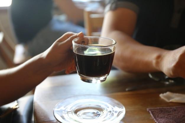 Couple de personnes avec un verre de café noir chaud et un gâteau sur une table en bois dans un café
