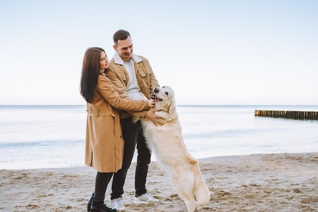 Couple à pied avec leur animal de compagnie golden retriever en bord de mer au jour d'automne