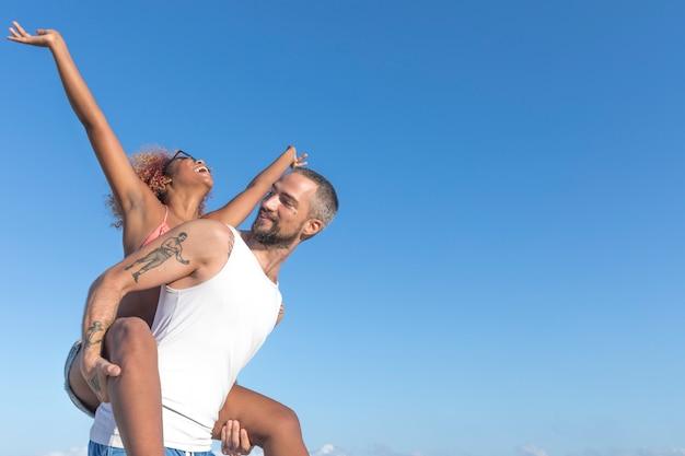 Couple piggy back sur la plage en été