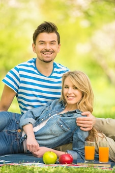 Un couple pique-nique dans un parc et boit du jus.