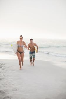 Couple avec planche de surf sur la plage