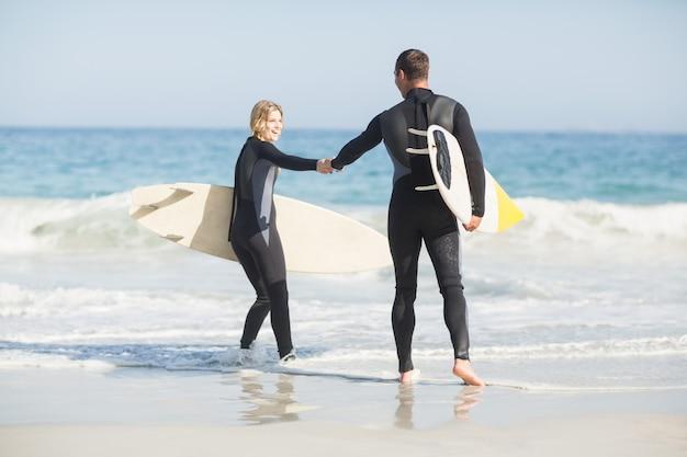 Couple, planche surf, tenant main, plage