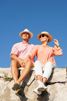 Couple plein coup assis sur la falaise
