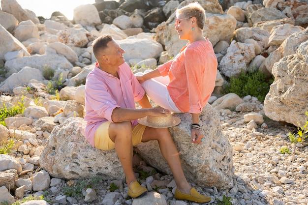 Couple plein coup assis sur des rochers