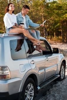 Couple plein coup assis sur la voiture