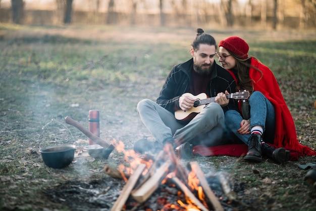 Couple plein plan près d'un feu de camp