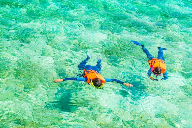 Couple de plongée en apnée dans l'île tropicale des maldives.