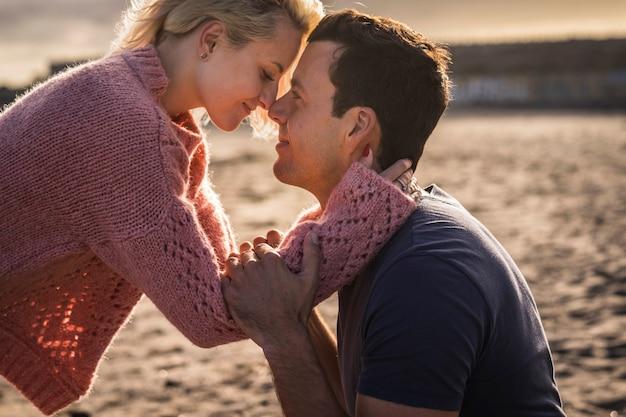 Couple plus proche dans un beau moment d'amour ensemble sentant l'émotion nez toucher le nez et étreindre avec passion la lumière du soleil dans la surface pour la tendresse et la passion de l'image douce romantique dorée