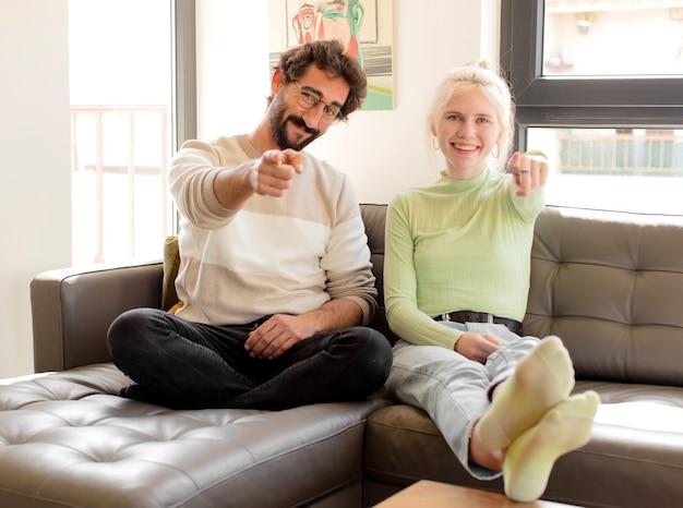 Couple pointant vers l'avant avec un sourire satisfait, confiant et amical, vous choisissant