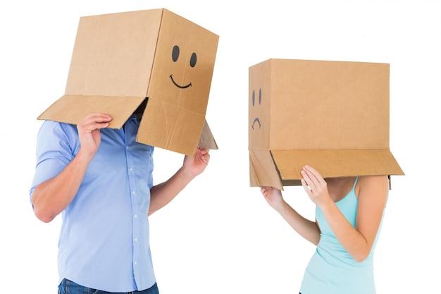 Couple portant des boîtes de visage émoticône sur leurs têtes