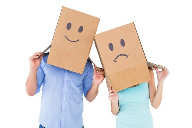 Couple portant des boîtes de visage triste sur leurs têtes