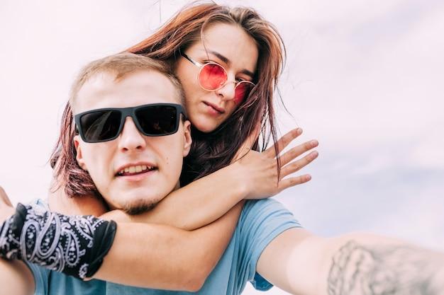 Couple portant des lunettes de soleil prenant selfie contre le ciel
