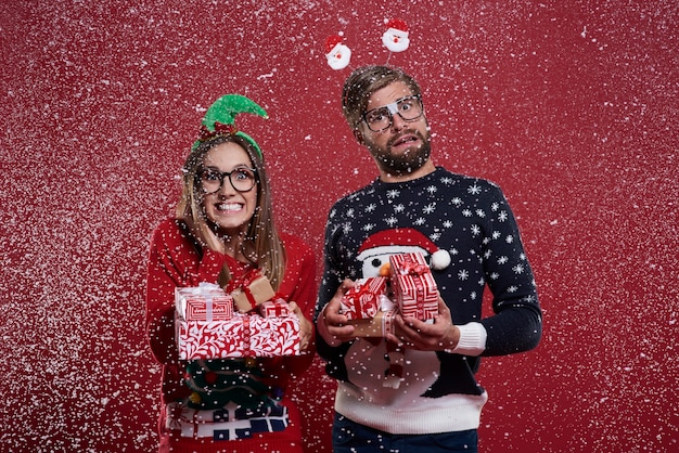 Couple portant une pile de cadeaux de noël