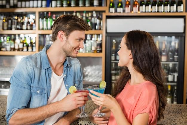 Couple portant un toast avec des cocktails