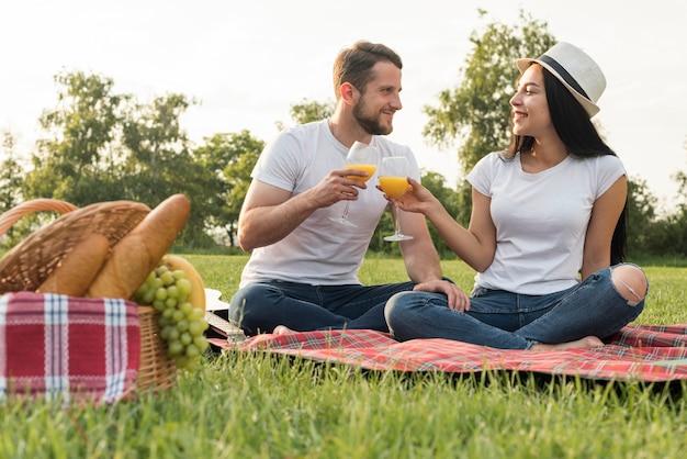 Couple portant un toast sur une couverture de pique-nique