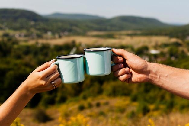 Couple portant un toast avec des tasses de café