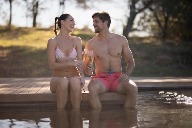 Couple portant un verre de champagne dans la piscine