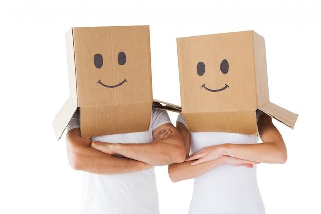 Couple portant des visages souriants sur leurs têtes
