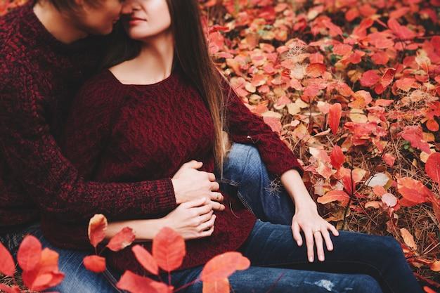 Couple porté dans des vêtements de style automne, la famille des pulls ressemble à travers le paysage d'automne. forêt couverte de feuillage jaune. promenade d'automne à l'extérieur.