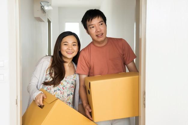Couple portez la boîte pour passer à la nouvelle maison