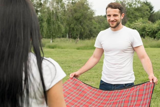 Couple posant une couverture de pique-nique