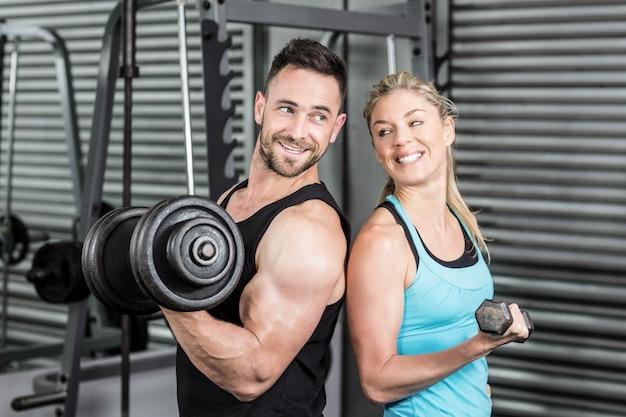 Couple posant avec des haltères au gymnase de crossfit