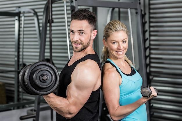 Couple posant avec des haltères au gymnase