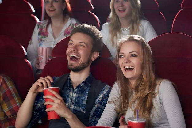 Couple positif de deux, petit ami en chemise à carreaux et petite amie en chemisier gris surpris souriant, regardant un film de comédie ensemble, tenant une tasse rouge avec du cola. meilleurs amis s'amusant à la salle de cinéma.