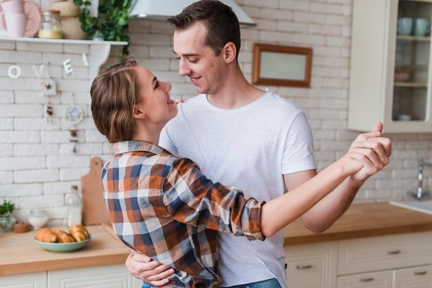 Couple positif embrassant et dansant dans la cuisine