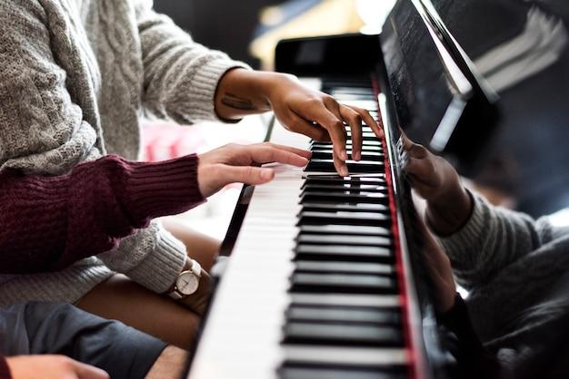Couple pratiquant sur un piano ensemble