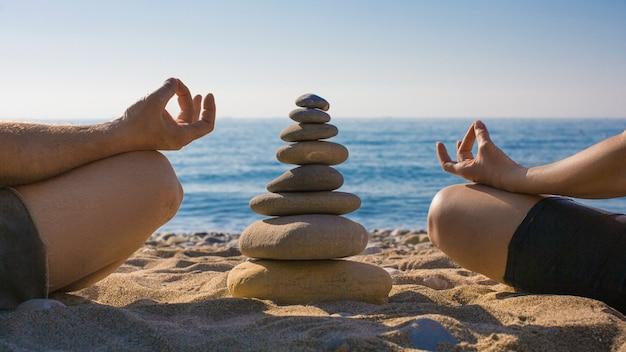 Couple pratiquant le yoga sur la plage. calme et relaxe. zen